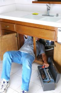 Plumber repairs a kitchen sink drain