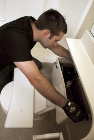 Sugar Land plumbing specialist opens a toilet tank for repairs