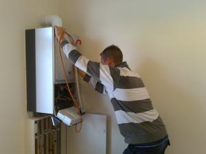 a Sugar Land plumber checks a water heater unit